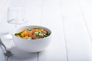 Hawaiian Poke salad with salmon, avocado and vegetables in a bowl on a white wooden rustic background with copy space, vegetables and a fork