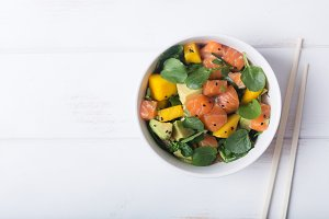 Hawaiian Poke salad with salmon, avocado and vegetables in a bowl on a white wooden rustic background with copy space