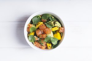 Hawaiian Poke salad with salmon, avocado and vegetables in a bowl in the center on a rustic background
