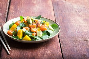 Hawaiian Poke salad with salmon, avocado and vegetables on the plate on a rustic background
