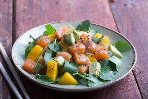 Hawaiian Poke salad with salmon, avocado and vegetables on the plate on a brown wooden rustic background