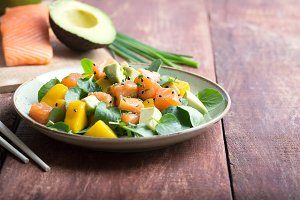 Hawaiian Poke salad with salmon, avocado and vegetables on a rustic background