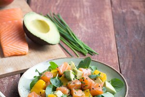 Hawaiian Poke salad with salmon, avocado and vegetables on a rustic background with copy space and vegetables on the background
