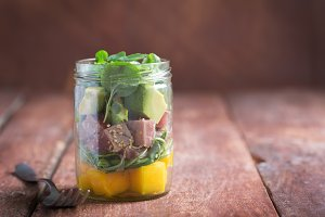 Hawaiian Poke salad with tuna, avocado and vegetables in a jar on a rustic background