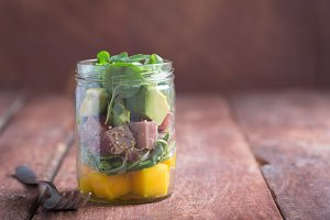 Hawaiian Poke salad with tuna, avocado and vegetables in a jar on a wooden rustic background