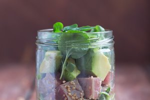 Hawaiian Poke salad with tuna, avocado and vegetables in a jar in the center on a rustic background
