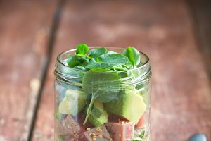 Hawaiian Poke salad with tuna, avocado and vegetables in a jar in the center on a wooden rustic background. Vertical