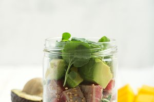 Hawaiian Poke salad with tuna, avocado, mango and vegetables in a jar with fork and vegetables on a white wooden rustic background, space for text above