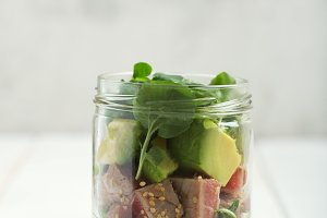 Hawaiian Poke salad with tuna, avocado, mango and vegetables in a jar on a white wooden rustic background