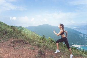 Slender young female athlete doing cardio exercise going up the mountain with sea in background.