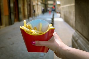 Holding typical french fries in hand in the streets of Brussels