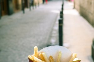Holding french fries in hand in the street, vertical, copy spacve