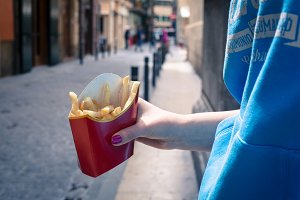 Holding french fries in hand in the street
