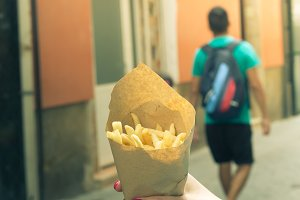 Holding typical potato fries in hand in the streets