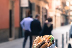 A girl holding a hamburger in hands. Summer, people in the street