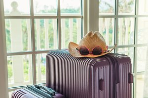 Purple suitcases, hat, sunglasses