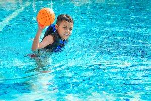 Happy boy in life jacket in pool