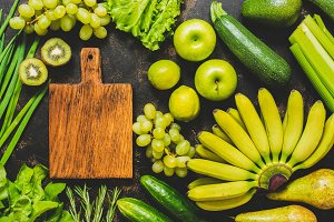 An empty cutting board and a frame of fresh green and yellow vegetables and fruits. Top view. Various vegetables and fruits.