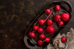 Fresh radish scattered on a ceramic rustic dish, dark background. Top view, copy space