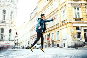 Young woman jumping on the street in town.