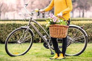 Young woman with bicycle standing outside in sunny spring.