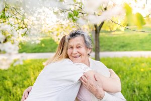Elderly grandmother and granddaughter hugging in spring nature.