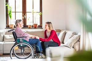 An elderly grandmother in wheelchair with an adult granddaughter at home.
