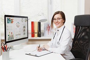Young smiling woman sitting at desk, working on computer with medical documents in light office in hospital. Female doctor in medical gown, stethoscope in consulting room. Healthcare, medicine concept