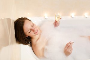 Attractive young sexy woman with long brown hair and straight naked body lying in white foam bath tub with candles around in light bathroom, drink alcohol from wine glass and smoke cigarette indoors.