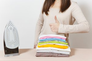 Close up cropped housewife in light casual clothes hold family clothing on ironing board with iron. Woman show thumb up isolated on white background. Housekeeping concept. Copy space advertisement.