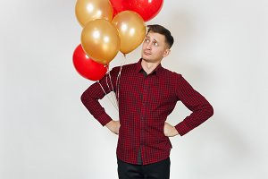 Handsome caucasian sad upset young y man 25-30 years in red plaid shirt with yellow golden balloons, celebrating birthday, on white background isolated for advertisement. Holiday, party concept.