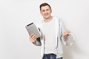 Young handsome smiling male student in blue jeans, t-shirt and light sweatshirt holds silver tablet pc computer and wireless headphones in hands isolated on white background. Concept of technology