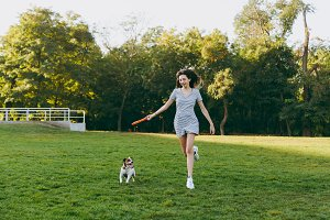 Girl throwing orange flying disk to small funny dog, which catching it on green grass. Little Jack Russel Terrier pet playing outdoors in park. Dog and owner on open air. Animal in motion background.