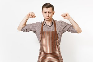 Young strong man chef or waiter in striped brown apron, shirt showing biceps, muscles isolated on white background. Male housekeeper or houseworker - looking camera. Domestic worker for advertisement.
