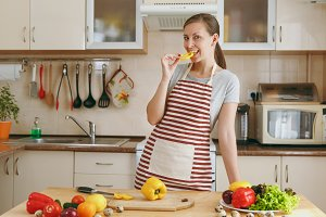 A young attractive woman in an apron tastes yellow pepper in the kitchen. Dieting concept. Healthy lifestyle. Cooking at home. Prepare food.