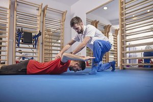 two people, physiotherapist checking patient back, lying down in exercise room.