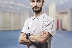 one young man, looking at camera, physiotherapist portrait. in blurred background exercising room.