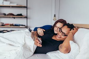 Smiling couple in bed with mobile