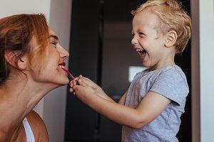 Little boy putting on makeup