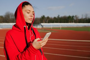 Side view of a young sport woman wearing a red hoodie. He is jogging and listening to music with his smartphone in hands.