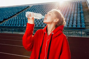 People, lifestyle and sport concept. Sport woman athlet overcame long distance, drinks water from plastic bottle, listens audio tracks in earphones.