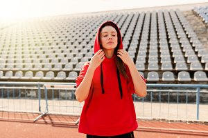 Beautiful lady runner in warm clothes on the stadium looking aside. Wearing red hood.