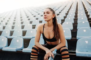 Sporty young attractive girl in sportswear relaxing after hard workout sit and drink water from bottle after running on a stadium