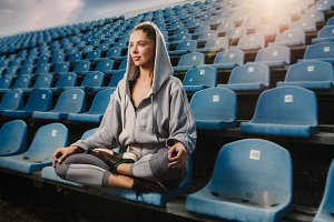 Young attractive woman practicing yoga, sitting in Padmasana exercise, Lotus pose on meditation session, working out wearing sportswear
