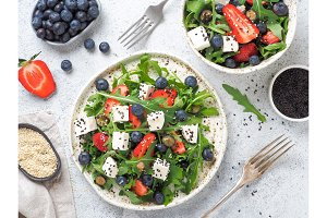 Salad with arugula, feta, strawberry, blueberry
