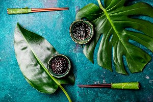 Asian food concept. Chopstick and soysauce soy sauce with white sesame on turquoise background with tropical leaves . Top view