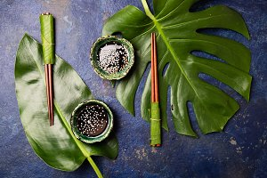 Asian food concept. Chopstick and soysauce soy sauce with white sesame on blue background with tropical leaves . Top view