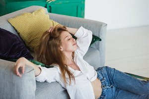 Young woman relaxing at cozy sofa in light room