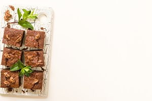 Brownie sweet chocolate dessert with walnuts and meant leaves on retro board with copy space on pastel beige background.