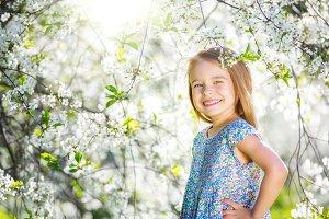 Happy little girl in cherry blossom garden